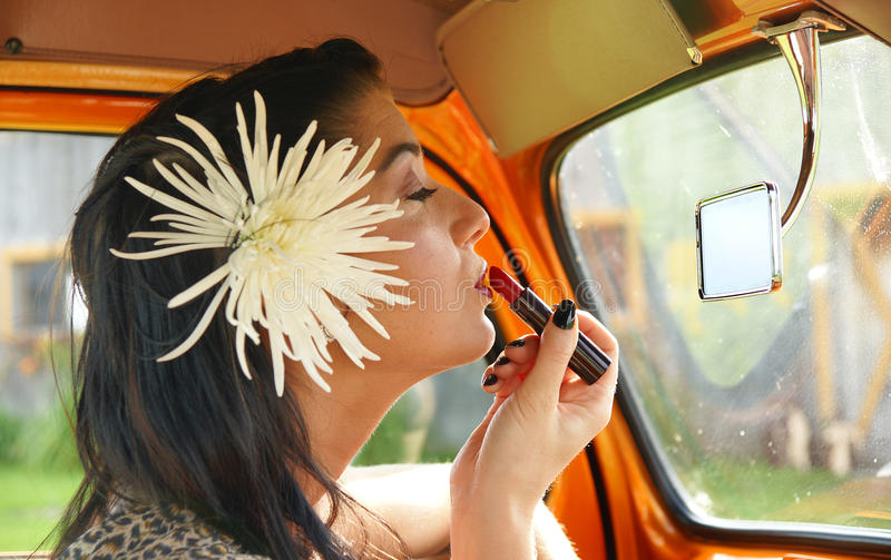 Girl applying lipstick. Inside the truck. front to the mirror stock photos