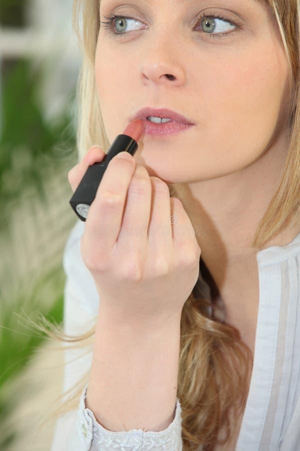 Girl applying lipstick royalty free stock images