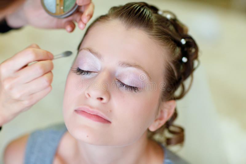 Girl applying make-up royalty free stock photo
