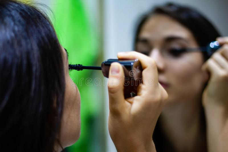 Girl applying mascara in the mirror. Adult, appearance, application, attractive, beautiful, beauty, brunette, brush, business, businesswoman, care, cosmetic royalty free stock image