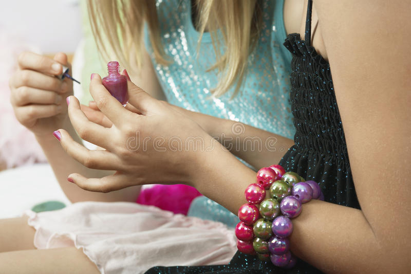 Girl Applying Nail Polish To Friend's Fingernails. Closeup midsection of a young girl applying nail polish to friend's fingernails stock photo