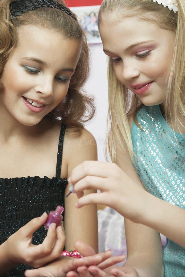 Girl Applying Nail Polish To Friend's Fingernails. Closeup of a young girl applying nail polish to friend's fingernails stock photos