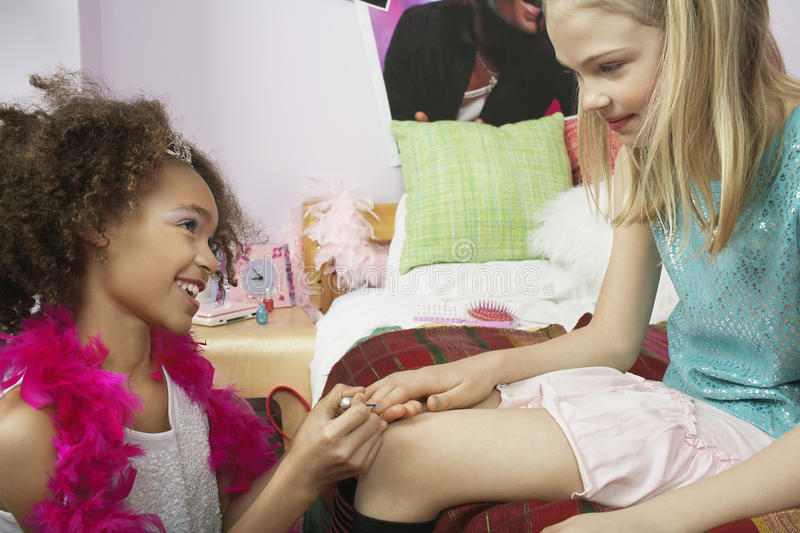 Girl Applying Nail Polish To Friend's Fingernails. Young girl applying nail polish to friend's fingernails, in the bedroom stock image