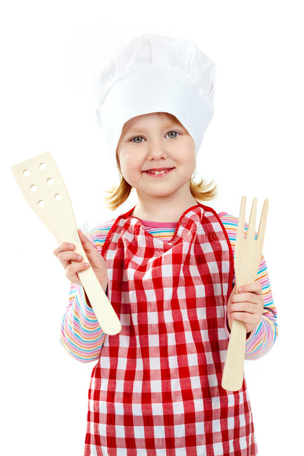 Ready to cook. Girl in an apron and cook cap holding wooden kitchen tools royalty free stock photos