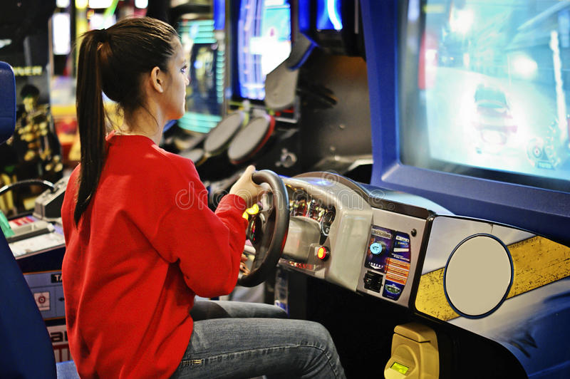 Girl in the arcade game. A teenager playing cars in amusument arcade in Houston, Texas stock images