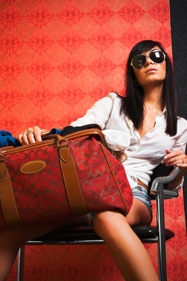 Girl in the armchair. Girl with bag in the armchair royalty free stock photo