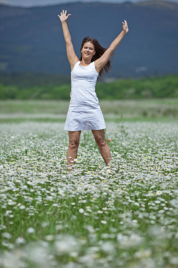 Girl with arms raised in chamomile field
