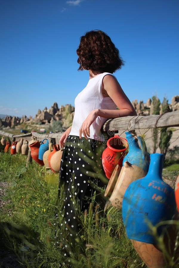 A girl around jugs in Cappadocia. Blue, wish, dreams, red, green, grass, sky, curls, white, t-shirt, summer, model, horizon, natural, nature, turkey, hands royalty free stock image