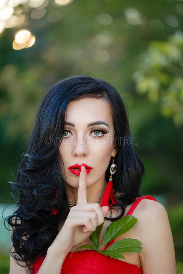 Girl in art deco style. Retro portrait. Attractive brunette girl in the red dress. Close-up portrait. Girl secret. She put a finger to his lips. Art Deco and stock photos