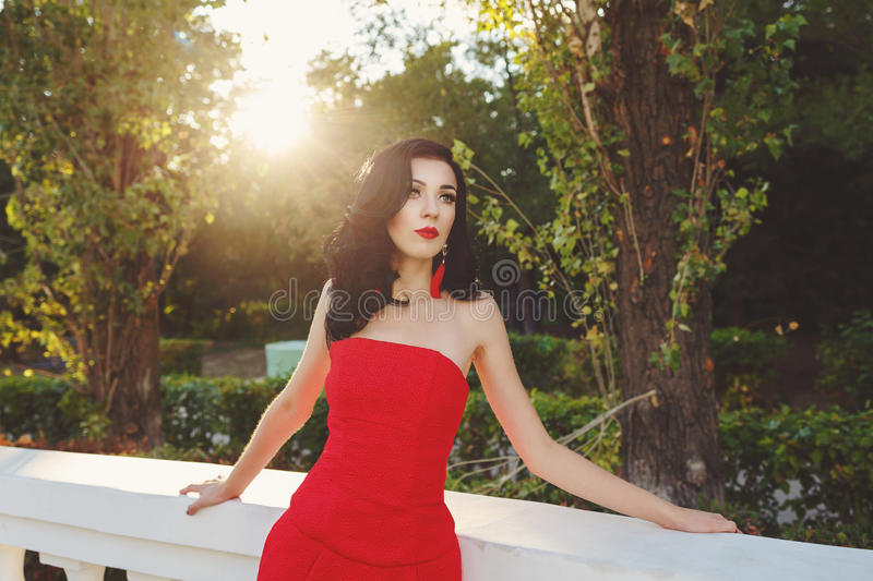 Girl in art deco style. Retro portrait. Attractive brunette girl in the red dress. Portrait at sunset. Art Deco and Art Nouveau. The concept of retro fashion royalty free stock photos