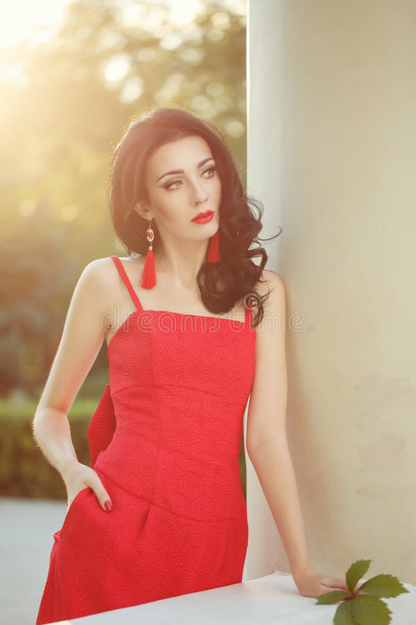 Girl in art deco style. Retro portrait. Attractive brunette girl in the red dress. Portrait at sunset. Art Deco and Art Nouveau. The concept of retro fashion stock photo