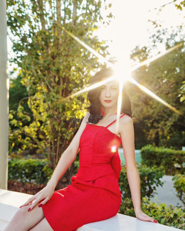 Girl in art deco style. Retro portrait. Attractive brunette girl in the red dress. Portrait at sunset. Sun glare in her hair. Art Deco and Art Nouveau. The royalty free stock photo