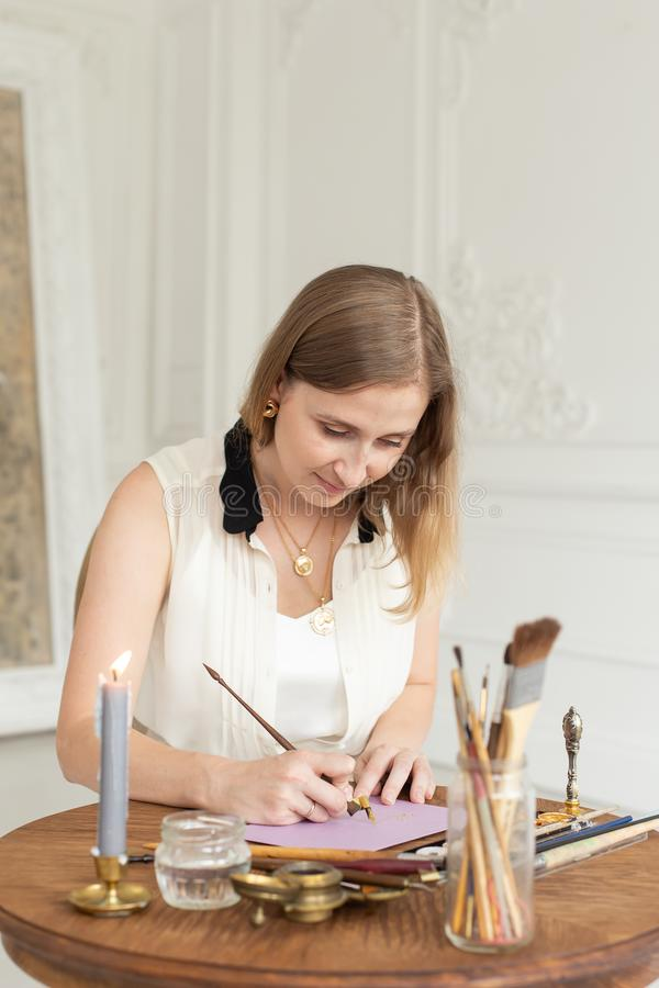 The girl artist is inspired and paints a picture. Holds a brush. Soft focus. Interior artist`s workshop. stock photo