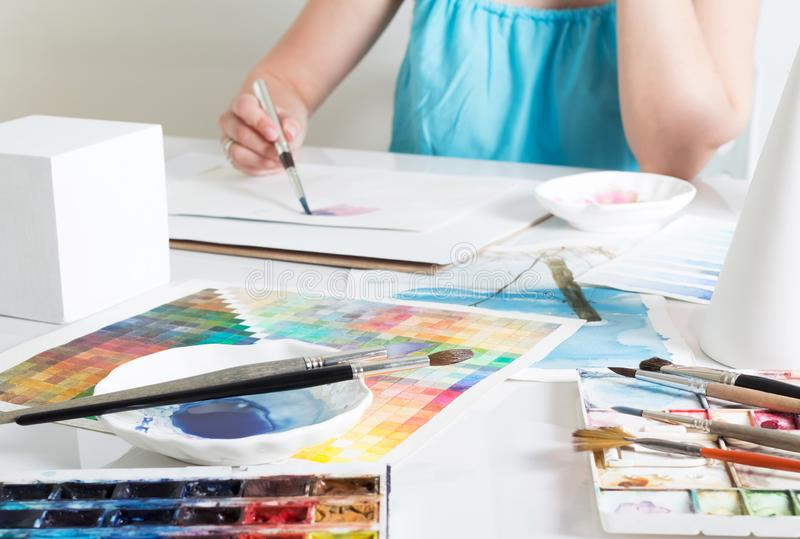 Girl artist painting picture with watercolours at desk in bright studio royalty free stock image