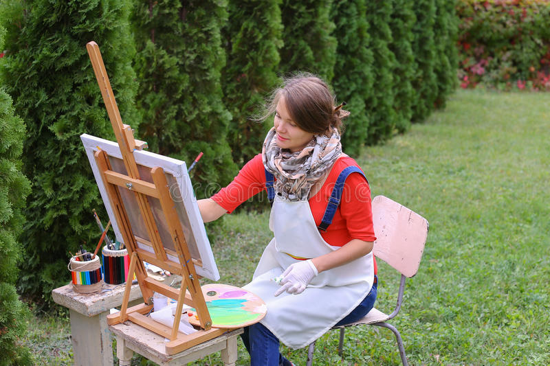 Girl artist paints picture and sits on chair at easel sides of t stock image