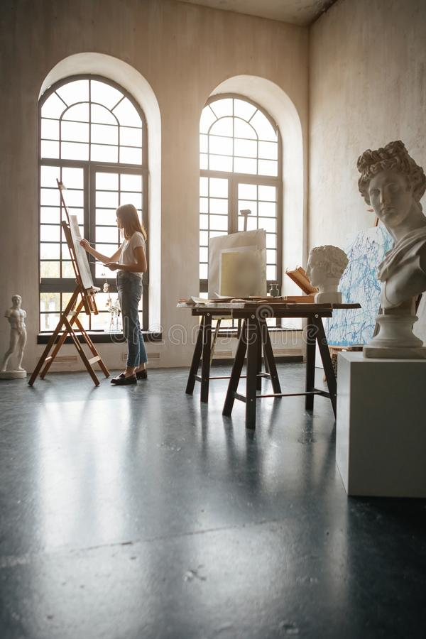 Girl artist working in the workshop light room. Creating a picture. Work with paints, brushes and easel. Creative. Inspired mood. Beautiful backlight. Vertical royalty free stock images