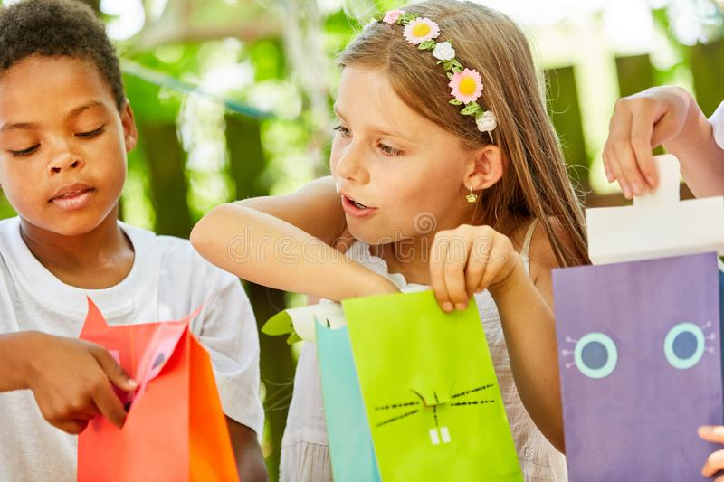 Girl as a birthday girl unpacks a gift. Girl as a birthday girl unpacks a present at the birthday party royalty free stock image