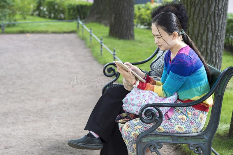 Asian girl sitting on a Park bench at the entrance to the Hermitage Museum of St. Petersburg, Russia, September, 2018 royalty free stock photos