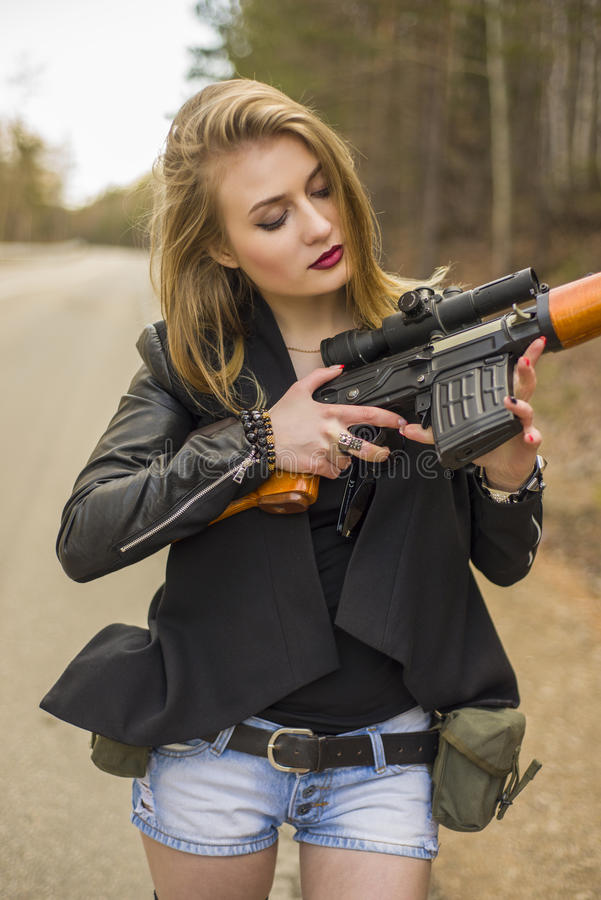Girl assassin waiting for his victim on the road. Holding her Dragunov sniper rifle SVD stock photos