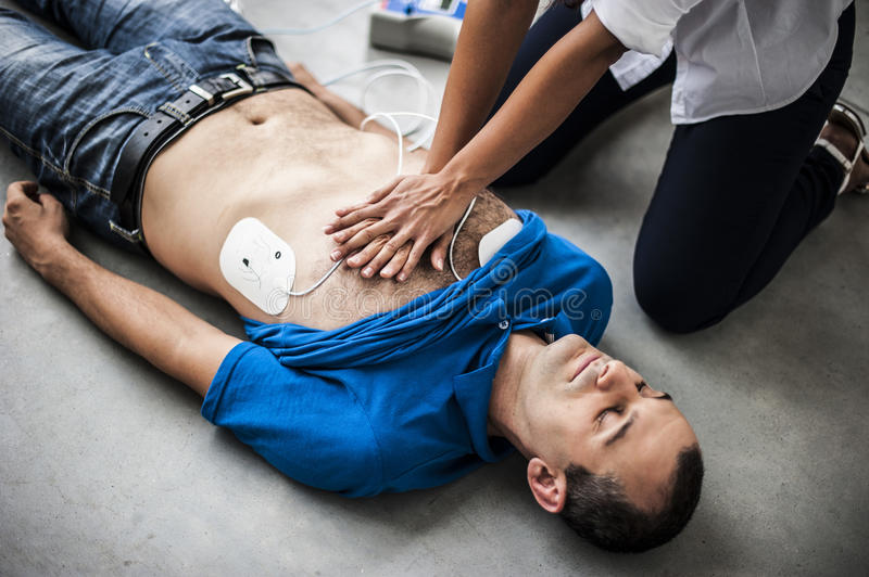 Girl assisting an unconscious man. Girl assisting an unconscious men after fatal accident with cardiopulmonary resuscitation and defibrillator royalty free stock images