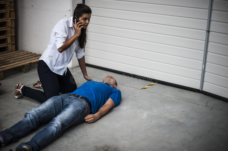 Girl assisting an unconscious man. Girl assisting an unconscious men after fatal accident with cardiopulmonary resuscitation and defibrillator royalty free stock photo