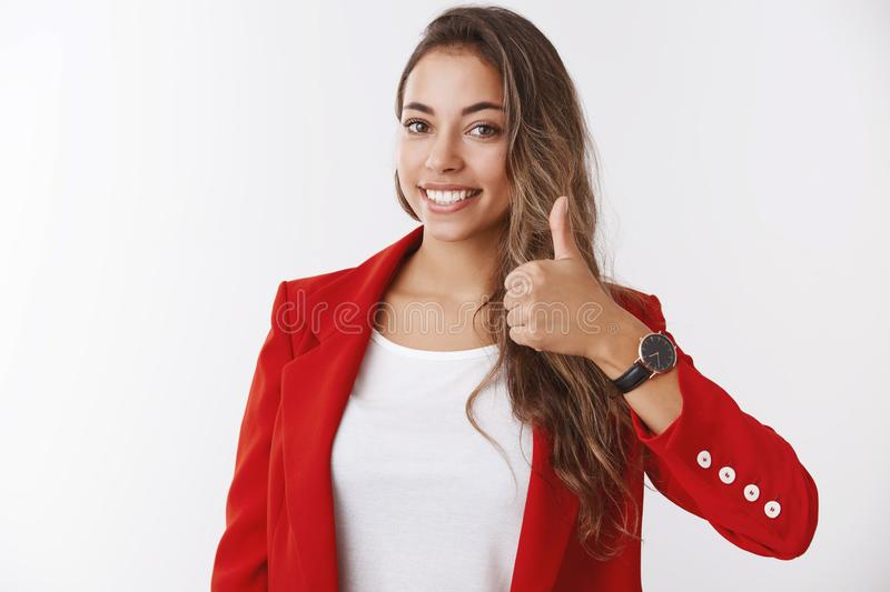 Girl assuring you have lucky day. Happy smiling gorgeous female entrepreneur showing thumb up, liking approving awesome. Idea delighted giving positive reply stock photo