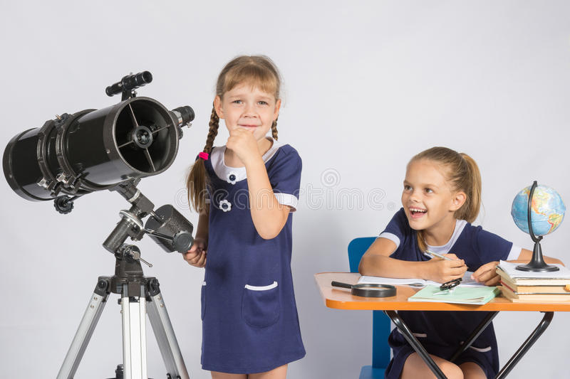 Girl astronomer thought, another girl with smile looking at her royalty free stock images