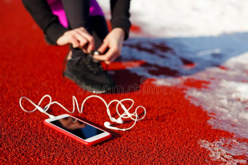 Girl athlete in black sneakers, crouching on the red track for running. near is a phone with wired headphones. Cold snowy weather.  royalty free stock photo