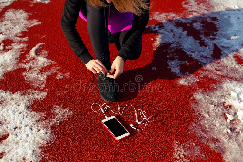 Girl athlete in black sneakers, crouching on the red track for running. near is a phone with wired headphones. Cold snowy weather.  stock photos