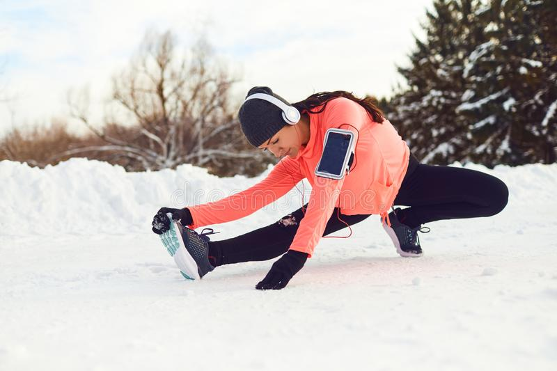 Girl athlete does stretching legs on the snow in winter. stock photography