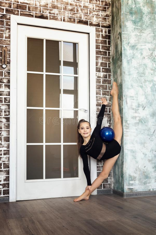 Girl athlete doing exercise gymnastics, doing an exercise with a blue sword in a vertical string royalty free stock photography