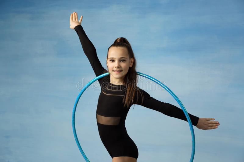 Girl athlete doing exercise gymnastics, looking at the camera doing an exercise with a hoop royalty free stock image