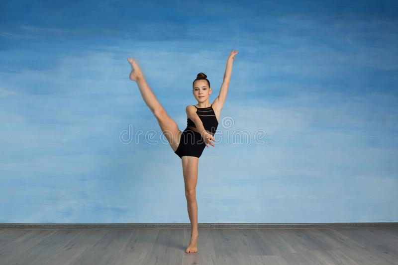 Girl athlete doing exercise gymnastics, looking at the camera stock photo