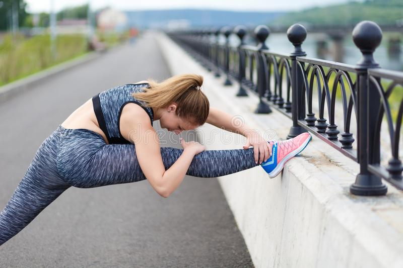 Girl athlete doing sports exercises workout on the waterfront stock photo