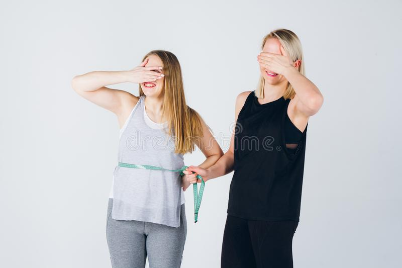 Girl athlete measures the size of the belly of her pregnant girl royalty free stock image