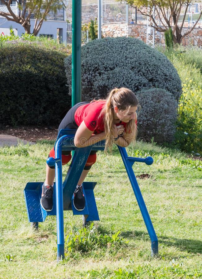 Girl athlete performs an exercise to strengthen the back on a street public simulator in the open air in Zefat city in Israel. Safed, Israel, April 13, 2019 royalty free stock image