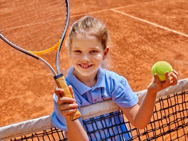 Girl athlete with racket and ball on tennis. Kid athlete in blue form with racket and ball on brown tennis court stock photography
