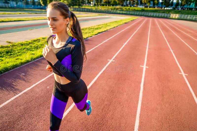 Girl athlete runs on the stadium at sunset royalty free stock photos