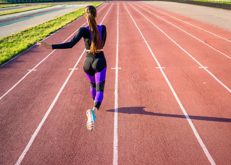 Girl athlete runs on the stadium at sunset stock photo