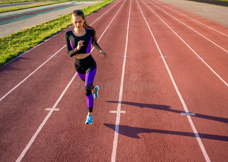 Girl athlete runs on the stadium at sunset stock photography