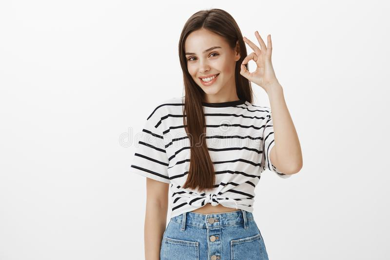 Girl attracts customers to her flower shop. Studio shot of positive confident european woman in striped t-shirt, raising stock image