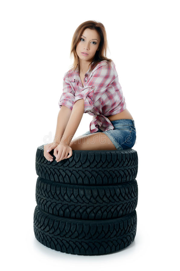 Girl with automobile tyres stock photography
