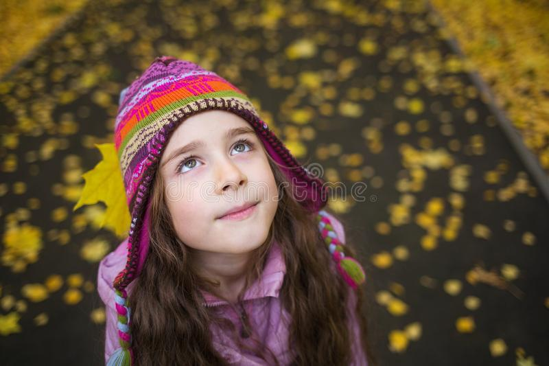Girl in autumn clothes and funny hat on the background of yellow leaves looking up to the right. stock image