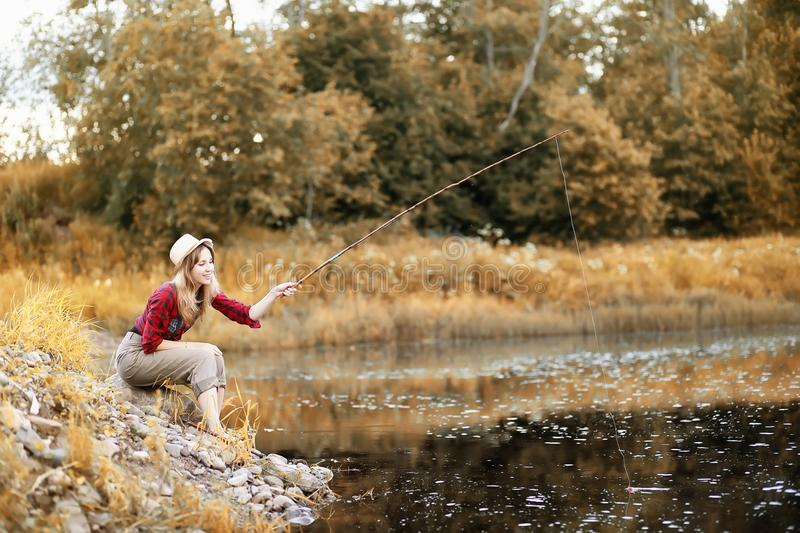 Girl in autumn with a fishing rod stock photos