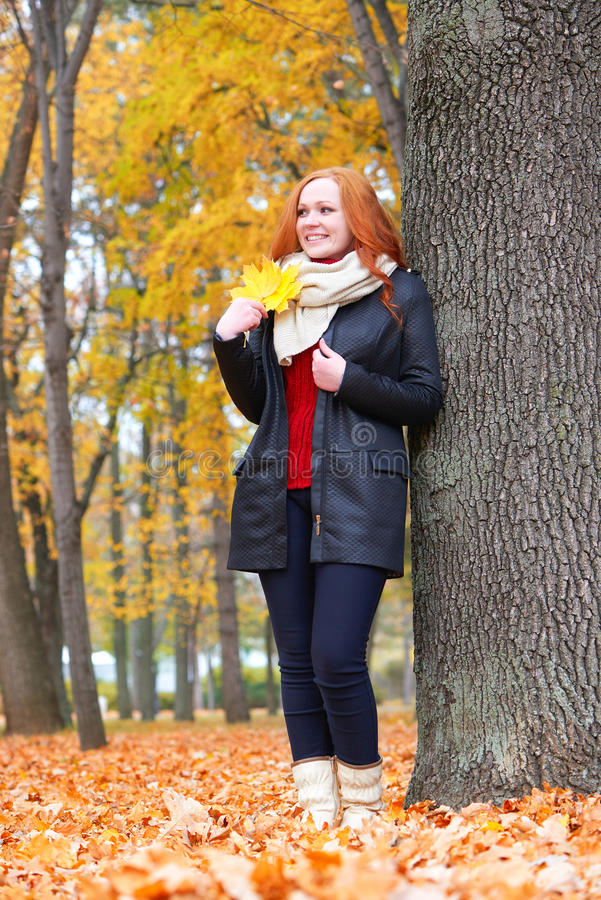 Girl in autumn forest keep leaves in the hands, stand near big tree stock photos