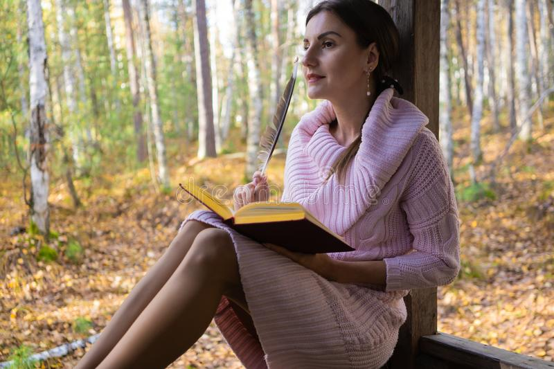 Girl in the autumn forest, reads a book, a woman sits near a tree in the autumn forest and holds a book in her hands royalty free stock images