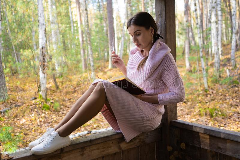 Girl in the autumn forest, reads a book, a woman sits near a tree in the autumn forest and holds a book in her hands stock photo