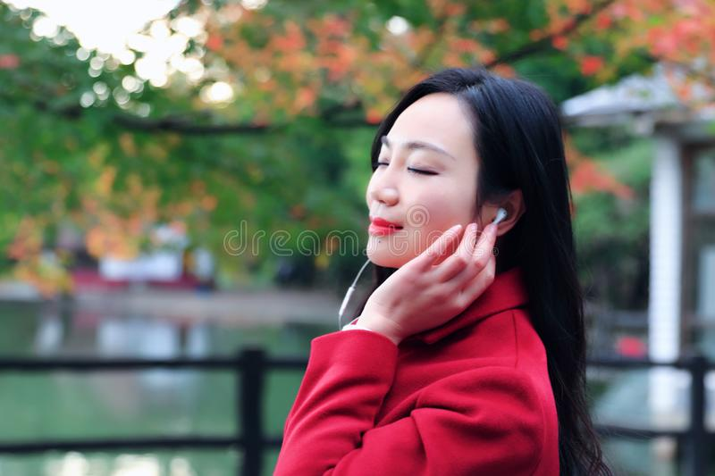 Girl in autumn garden. Asian Chinese Portrait Girl in the autumn garden and Music headphones woman stock images