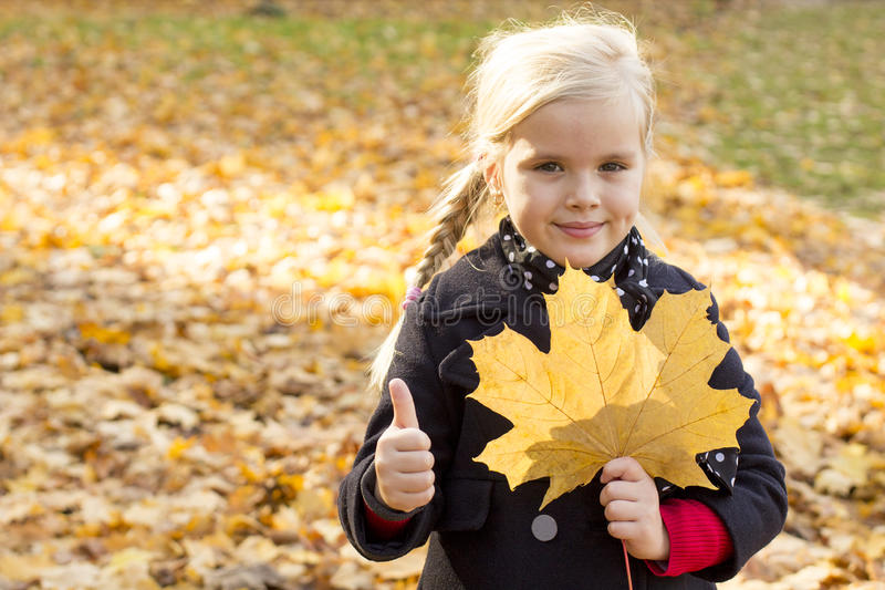 Girl with autumn leaf stock photos