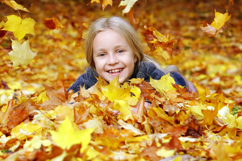 Girl in autumn leaves royalty free stock photos